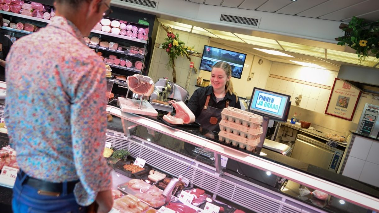 Student helpt klant in slagerij