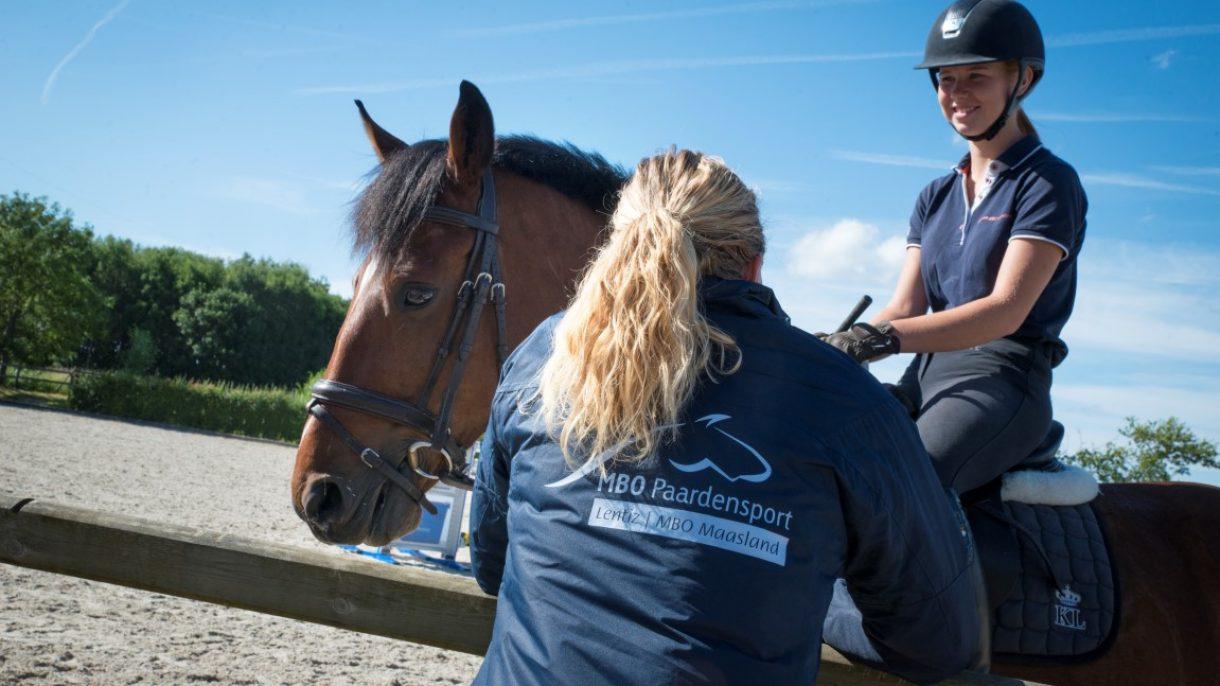 Student te paard en meisje bij hek
