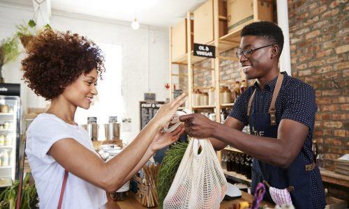 Jongen geeft tasje aan meisje in winkel