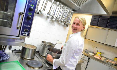 Studente in keuken achter pannen
