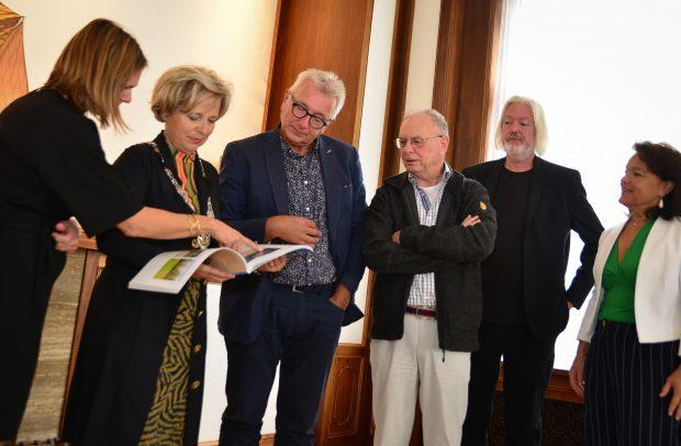 De burgemeester krijgt uitleg over het jubileumboek.