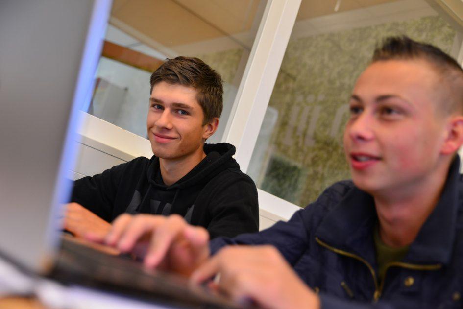 Jongens achter de laptop, een kijkt en lacht