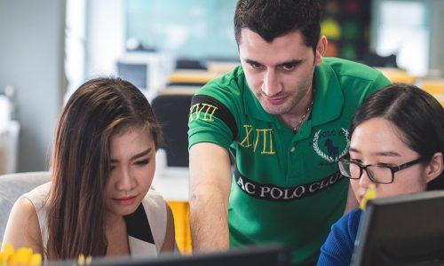 vwo docent met twee leerlingen op computer