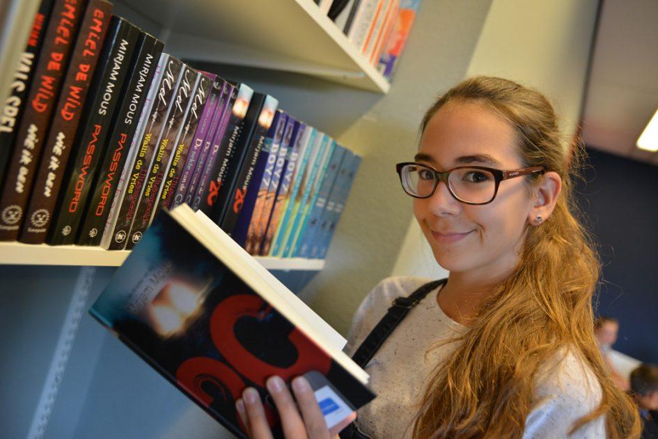 Leerling pakt een boek uit de boekenkast.