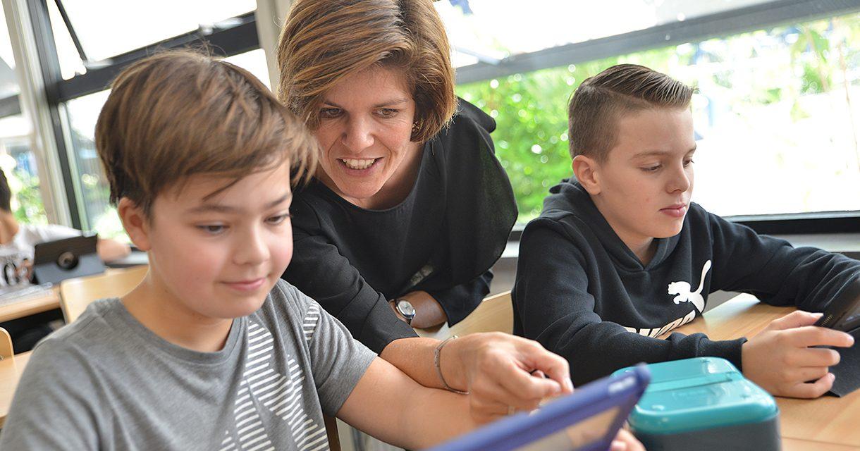 docent en leerlingen werken op iPad