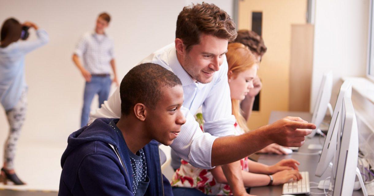Man wijst iets aan op computerscherm voor student